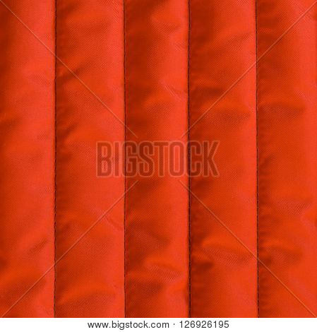 Red orange quilted textiles with insulation. Vertical stripes. Close up fragment of the top view.
