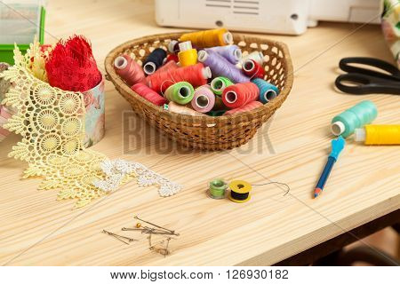 sewing accessories and threads in a basket lie on a table