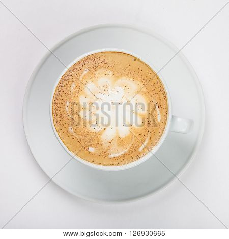 Delicious cappuccino in a white cup on the plate on white background. Close up top view.