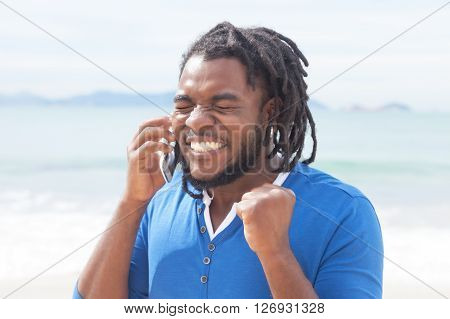 African american guy with dreadlocks receiving good news at phone outdoor at beach with ocean in the background