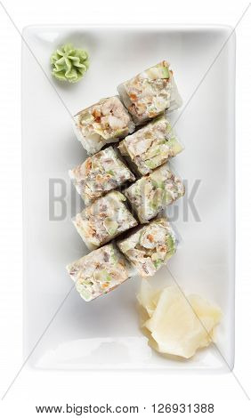 Sushi rolls with tuna and flying fish roe on a plate with wasabi and ginger. Top view. Isolated on white background. Include clipping path.
