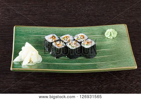 Sushi rolls on a plate with flying fish roe on dark brown wooden table. Side view.
