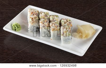 Sushi rolls on a plate with tuna and ginger on dark brown wooden table. Side view.