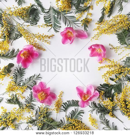 Overhead view of bouquet of yellow mimosa and pink tulip pattern isolated on white background