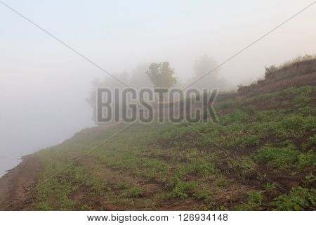 Mysterious Volga riverside in fog. Misty dawn early morning nature grassland landscape view in Russian countryside.