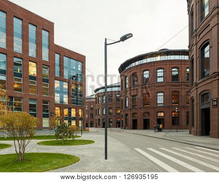 Extensive office complex exterior in loft style. Red brick buildings of former factory gasholders. Evening artitecture lighting street lamps.