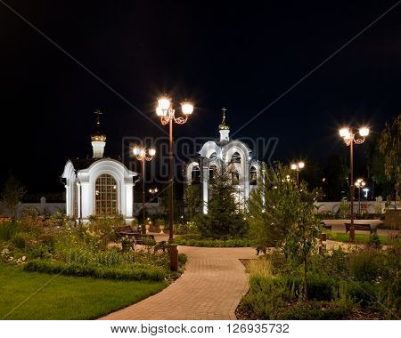 Orthodox temple complex. Architectural lighting. Internal territory of the complex. Street lamp in classic style chapel and bell tower. Sidewalks and landscaping