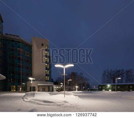 Street lamps of the office complex. Lighting supports and lamps. Winter snow evening.