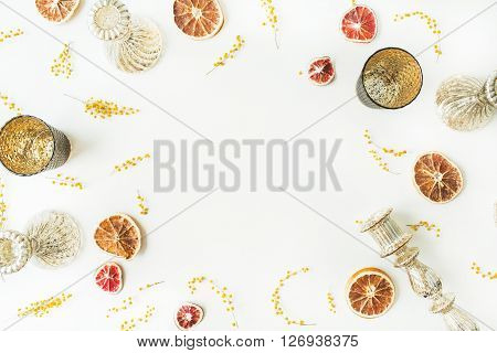 frame with dry oranges candlesticks branches of mimosa isolated on white background. flat lay overhead view