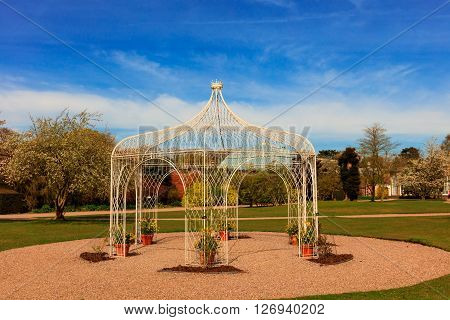 Wrought iron pergola in a landscaped park.