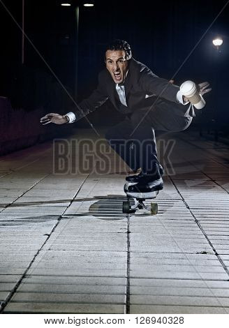 attractive and successful businessman riding skateboard wearing suit and necktie holding take away coffee looking excited and happy in trendy modern executive business people concept