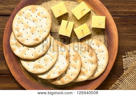Saltine or soda crackers with cheese pieces served on plate photographed overhead on dark wood with natural ight