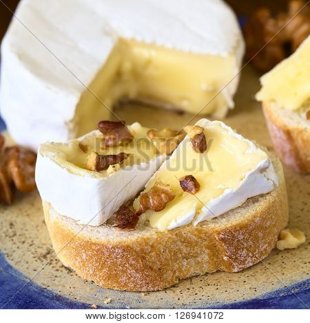 Baguette with camembert cheese and walnuts photographed with natural light (Selective Focus Focus on the first walnut pieces on the bread)