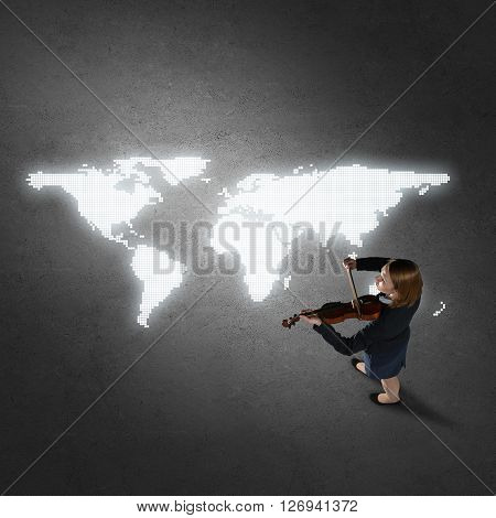 Top view of businesswoman playing violin and glowing world map on concrete floor