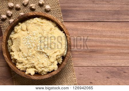 Chickpea spread or hummus with sesame seeds in wooden bowl photographed overhead on wood with natural light (Selective Focus Focus on the top of the spread)