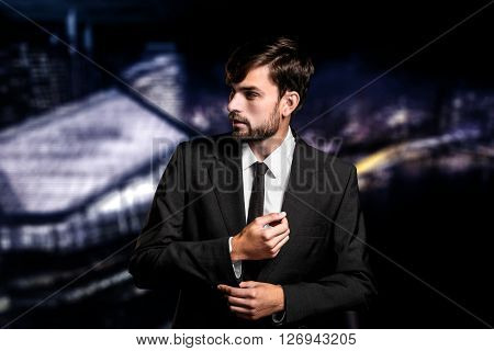 Stylish young businessman on night cityscape background. Businessman looking aside and correcting cuffs