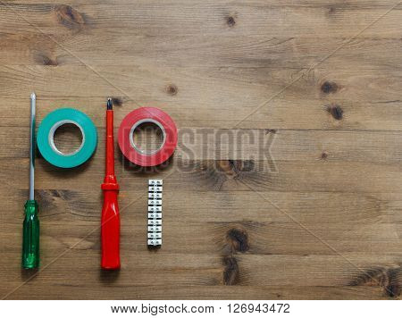 multicolored screwdrivers insulating tapes and electric block on wooden table