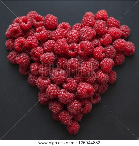 Summer ripe raspberry in the shape of hart