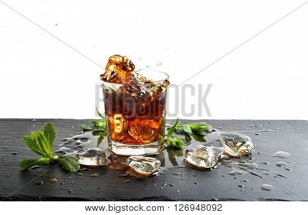 Glass of cola drink with ice and mint leaves. Cola splash. Food and beverages