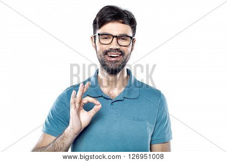Portrait of stylish handsome young man isolated on white background. Man cheerfully smiling, wearing glasses, showing ok sign and looking at camera