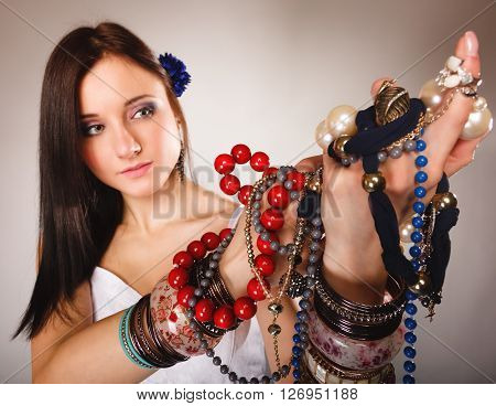 Beauty young woman in summer style with plenty of jewellery beads in hands gray background