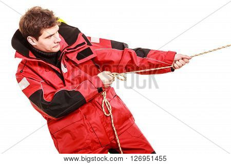 Young man pulling rope. Male in waterproof coat. Adventure danger concept.