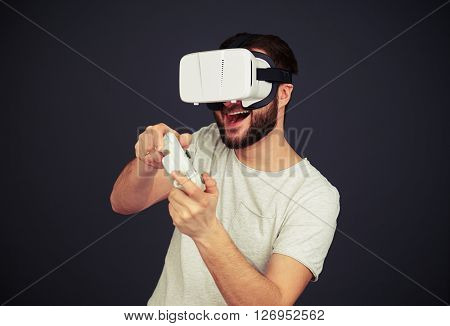 Beard man is playing on the joystick wearing hi-tech VR headset, on black background