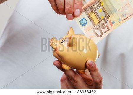 Spending money concept. Male hands with piggybank and euro banknote cash hang on laundry line. Savings.