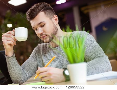 Cheerful male student is studying with concentration. He is sitting at desk and writing. The guy is drinking a cup of coffee