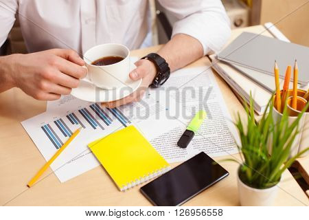 Close up of male arms holding a cup of coffee. Man is sitting at table near papers and mobile phone