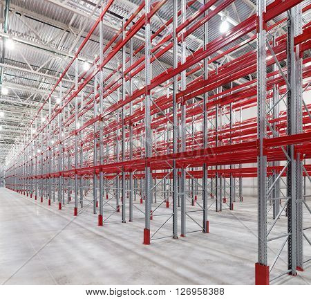 Industrial racks pallets shelves in huge empty warehouse interior. Storage equipment.