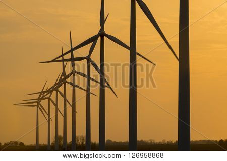 Wind turbine generator windmills backlit silhouetted in sunlight with clouds