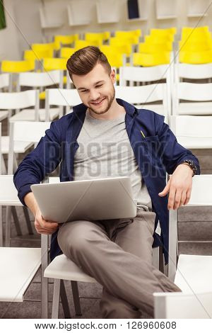 Handsome young man is using a laptop in auditory hall. He is sitting on chair alone and smiling