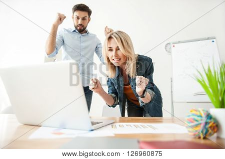 Cheerful two colleagues are standing near a laptop with anticipation. They are holding fists and looking at the screen with hope