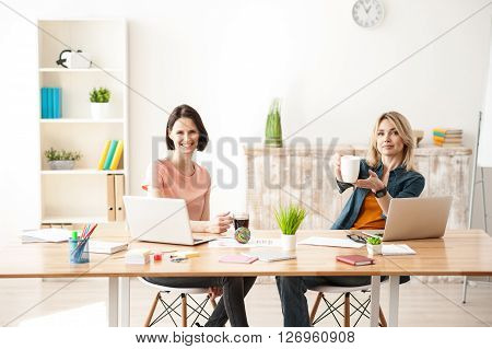 Help yourself with cup of coffee. Beautiful young women are making a break after work. They are sitting at desk in office and smiling. Blond girl is stretching forward a cup