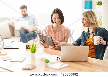 Cheerful two women are resting at office after work. They are sitting at desk and smiling. The woman is holding a tablet. Her colleague is pointing finger at it with interest