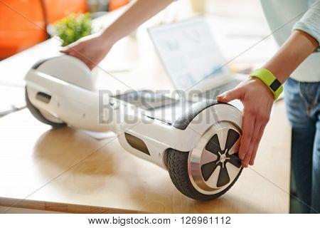 A good bargain. Close up of gyro scooter in hands of pleasant man who is holding it on the surface of table