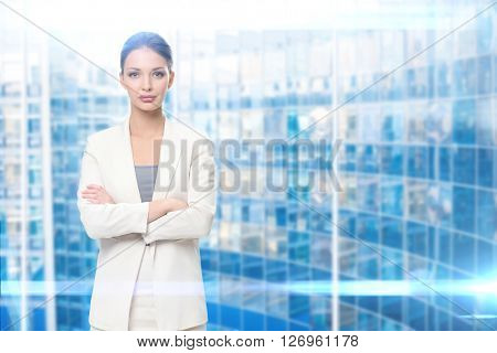 Half-length portrait of businesswoman with arms crossed, blue background. Concept of leadership and success
