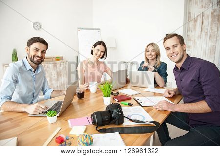 We like our work. Cheerful four workers are sitting at the desk and smiling. They are looking at camera happily