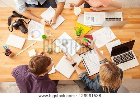 Top view of smart blond woman sharing her ideas with her team. She is holding and document and showing it with confidence. Woman and men are looking at it with satisfaction