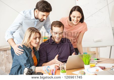 Attractive young man is showing a presentation on laptop and explaining his ideas. His colleagues are standing and listening to him attentively. They are smiling