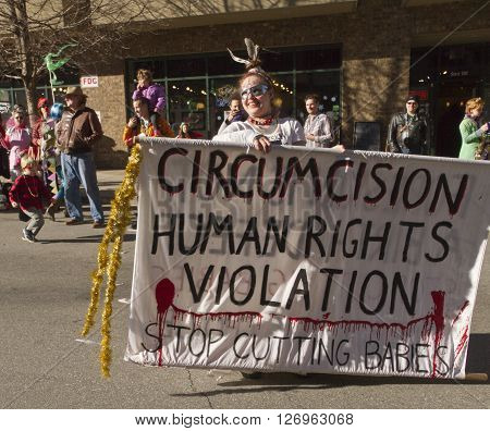 Asheville, North Carolina, USA - February 7, 2016: Costumed young woman holds large sign saying