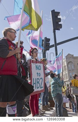 Asheville, North Carolina, USA - April 2, 2016: LGBT protest rally against the HB2 Law in North Carolina with symbolic flags transgender symbols and signs about bathroom restrictions pride and love