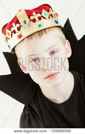 Serious Boy Wearing Crown And Black Gown