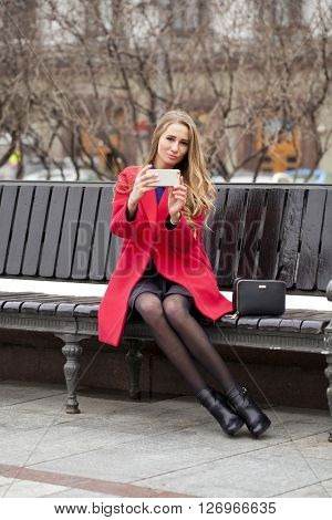 Young beautiful blonde woman calling by phone in red coat sitting on a bench in the spring street