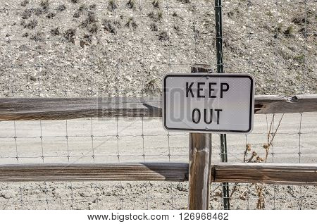 Serious keep out sign in front of a tall wire fence with wood rails and metal stakes to help enforce the message