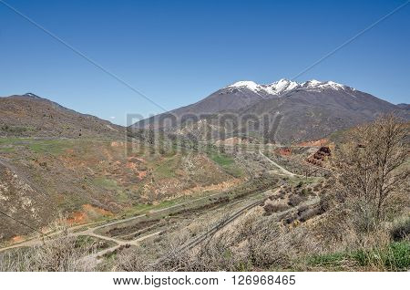 Beautiful rural scene with railroad tracks a highway dirt roads a river and snow topped mountains.