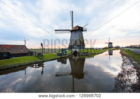 Traditional windmills in a dutch landscape in the Netherlands at sunset