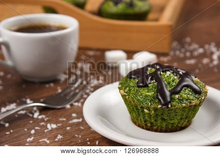 Homemade muffins baked with wholemeal flour with spinach desiccated coconut and chocolate glaze cup of coffee delicious healthy dessert or snack