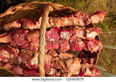 Crude shish kebab skewer in a basket